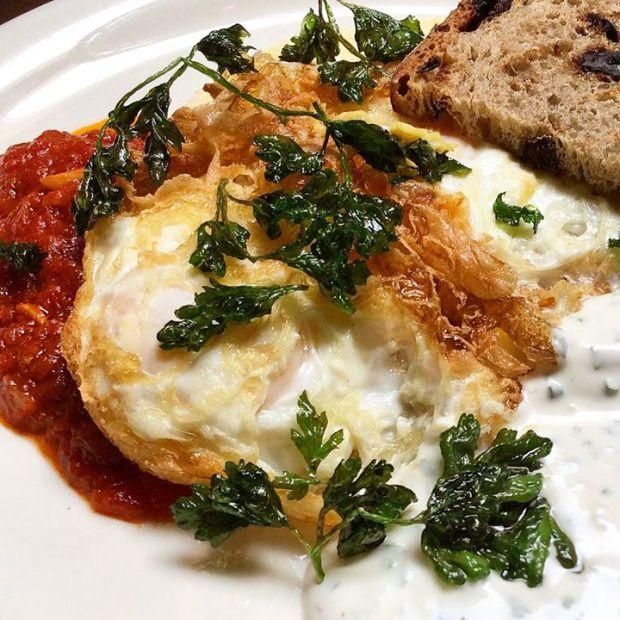 Fried eggs, creamy polenta, roasted tomato, herb créme fraiche & crispy parsley.